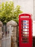 Britse telefooncel naast een poort stock foto's