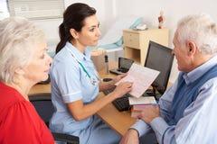Britse verpleegster die aan hoger paar spreekt Royalty-vrije Stock Afbeelding