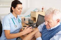 Britse verpleegster die injectie geeft aan de hogere mens Stock Afbeeldingen