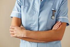 Britse verpleegster die zich met gevouwen wapens bevindt Royalty-vrije Stock Foto's