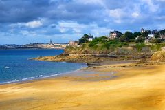 Brittany atlantic coast with St Malo and Dinard towns. Sand beach Plage Saint-Enogat in Dinard, with view to St Malo Old town and English Channel, Brittany Stock Photo