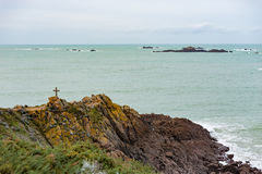 Brittany seascape with a cross on rocks and clouds on the horizo Stock Photo