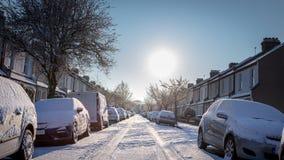 Brittisk bostads- gata med bilar och vägen som täckas i snö arkivfoto