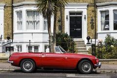 Brittisk plats Engelsk plats MG B klassisk bil som parkeras utanför radhus arkivfoto