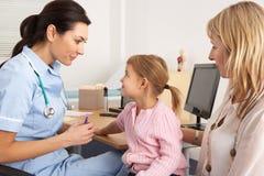 Brittisk sjuksköterska omkring som injicerar ungt barn Royaltyfria Bilder