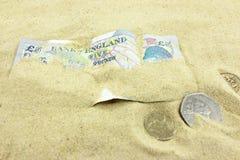 Brittisk valuta som begravas av sand Arkivfoto