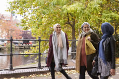 Brittiska muslimska kvinnliga vänner som går i stads- miljö Arkivfoton