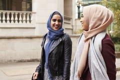 Brittiska muslimska kvinnliga vänner som går i stads- miljö Royaltyfri Foto