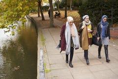 Brittiska muslimska kvinnliga vänner som går vid floden i stad Arkivfoton