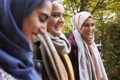 Brittiska muslimska kvinnliga vänner som möter i stads- miljö Arkivfoton