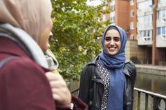 Brittiska muslimska kvinnliga vänner som möter i stads- miljö Royaltyfria Foton