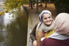 Brittiska muslimska kvinnliga vänner som talar vid floden i stad Royaltyfria Foton