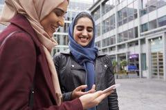 Brittiska muslimska kvinnor som smsar på mobiltelefonen utanför kontor Arkivfoto
