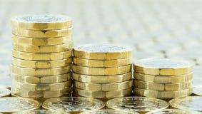 Brittiska pengar, tre pundmynt som stiger ned buntar Arkivbild