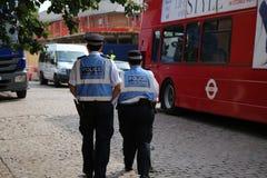 Brittiska poliser med högt synligt patrullera för blåa omslag royaltyfri fotografi