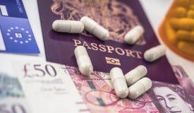 Brittiskt pass och europeiskt sjukförsäkringkort tillsammans med flera kapslar, begrepp av medicinsk förhöjning i krisen av arkivfoto