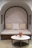 Brittiskt stiluppehällehörn med soffan och tabellen mot tegelstenväggen Royaltyfri Foto