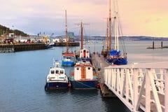 BRIXHAM, DEVON, GROSSBRITANNIEN, AM 2. NOVEMBER 2015: Kleine Boote machten an einer Anlegestelle im Hafen bei Sonnenaufgang fest Stockfoto