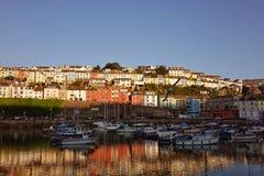 Brixham hamnhamn Devon England UK med färgade kulöra hus i bakgrunden och reflexionerna Arkivbilder