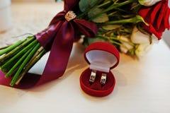 Bröllopbukett av den röda och vita rosen och bandet med bröllopri Arkivfoto