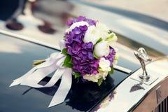 Bröllopbukett på en bröllopbil Arkivbild