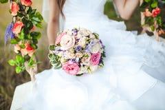 Bröllopbukettslutet upp i händer av bruden på den vita klänningen, gunga dekorerade med blommor Royaltyfri Foto
