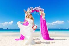 Bröllopceremoni på en tropisk strand i lilor Lycklig blond brid Royaltyfria Bilder
