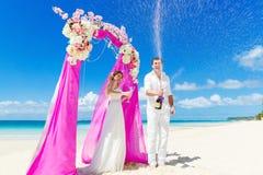 Bröllopceremoni på en tropisk strand i lilor Lycklig brudgum och Royaltyfri Fotografi