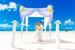 Bröllopceremoni på en tropisk strand i vit Lycklig brudgum och b Royaltyfria Bilder