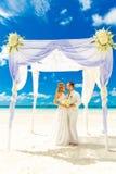 Bröllopceremoni på en tropisk strand i vit Lycklig brudgum och b Royaltyfri Fotografi