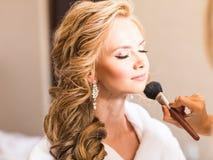 Bröllopmakeupkonstnär som gör ett smink för brud Härlig sexig modellflicka inomhus Blond kvinna för skönhet med lockigt hår Arkivfoto