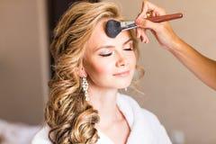 Bröllopmakeupkonstnär som gör ett smink för brud Härlig sexig modellflicka inomhus Blond kvinna för skönhet med lockigt hår Fotografering för Bildbyråer
