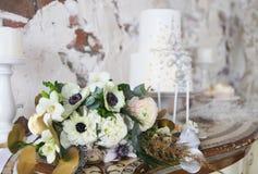 Bröllopstårtan med silvergarnering och bröllopbuketten med körde Royaltyfria Foton