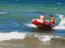 Bränningräddningsaktionfartyg med män i handling Arkivfoton
