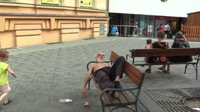 BRNO, CZECH REPUBLIC - AUGUST 11, 2015: Authentic emotion homeless man asleep on a bench, Europe, EU stock video footage