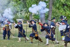 Historical reenactment Day of Brno. Actors in historical Infantry costumes shoot a musket, gunpowder smoke is around them royalty free stock photos