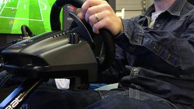 Gamers play video game consoles with steering wheel simulators