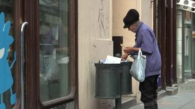BRNO, CZECH REPUBLIC, JULY 16, 2015: Authentic homeless woman looking and eats food from the trash bin stock video footage