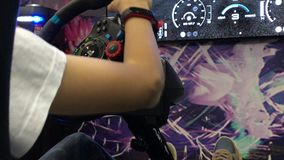 Young gamer playing video game console with steering wheel