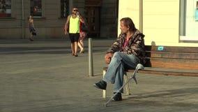 Brno, República Checa 11 de agosto de 2016: homem desabrigado deficiente da emoção autêntica que senta-se em um banco e em comer video estoque