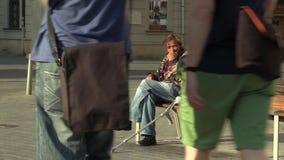 Brno, República Checa 11 de agosto de 2016: homem desabrigado deficiente da emoção autêntica que senta-se em um banco e em comer filme