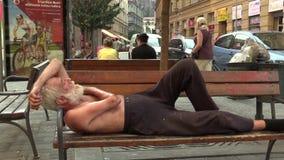 BRNO, REPÚBLICA CHECA, O 11 DE AGOSTO DE 2015: Homem desabrigado da emoção autêntica adormecido em um banco vídeos de arquivo