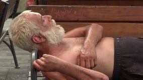 BRNO, REPÚBLICA CHECA, O 11 DE AGOSTO DE 2015: Homem desabrigado da emoção autêntica adormecido em um banco video estoque