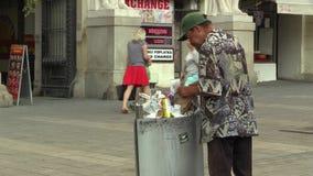 BRNO, REPUBBLICA CECA, L'11 AGOSTO 2017: L'indigente senza tetto autentico che guarda e mangia l'alimento dal bidone della spazza stock footage