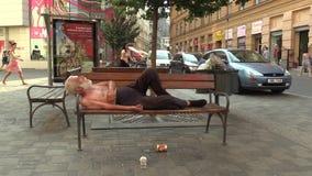 BRNO TJECKIEN, AUGUSTI 11, 2015: Hemlös man för autentisk sinnesrörelse sovande på en bänk arkivfilmer