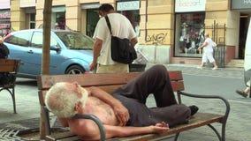 BRNO, TSJECHISCHE REPUBLIEK, 11 AUGUSTUS, 2015: Authentieke emotie dakloze mens in slaap op een bank en lopende mensen stock video