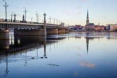 Bro över den djupfrysta floden i snöig vinterRiga citiscape under s Royaltyfri Bild