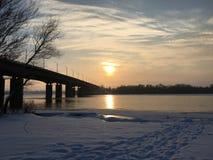 Bro över den djupfrysta floden på solnedgången royaltyfria bilder