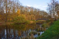 Bro över den gamla floden i parkera under sista soliga dagar av nedgången arkivfoton
