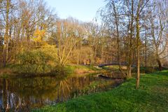 Bro över den gamla floden i parkera under sista soliga dagar av nedgången Arkivbild